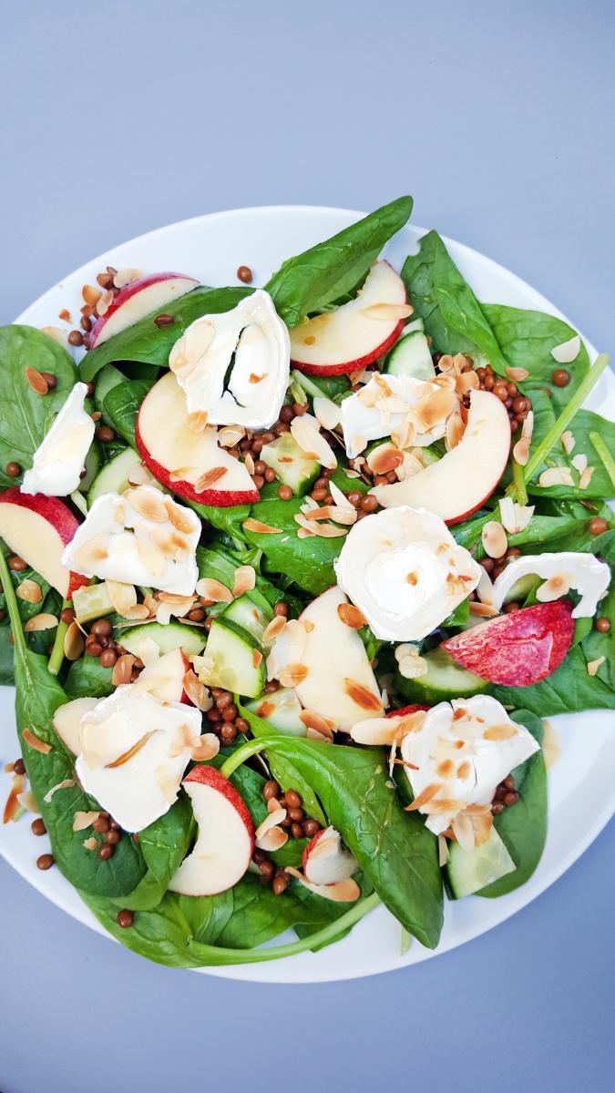 Salade van spinazie, geitenkaas, appel en linzen met honing en amandel